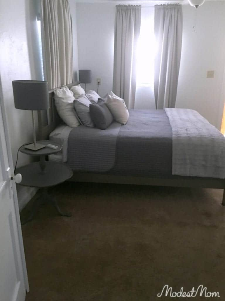 Simple but clean bedroom with throw pillows, a nice coordinating bedspread and curtains.