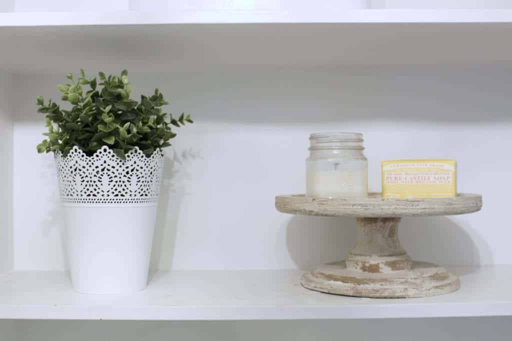 Laundry Room Makeover. Wooden stand with candle from Grove and Ikea white pot and greenery.