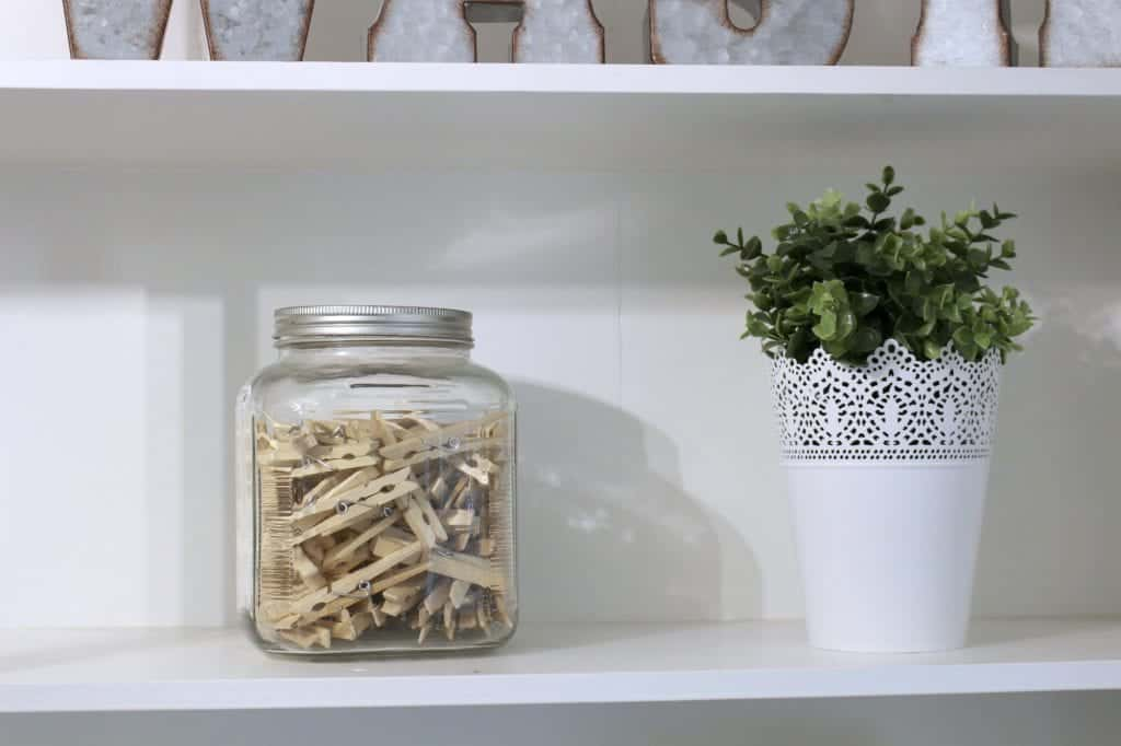 Laundry Room Makeover. Glass jar with clothespins and white jar and greenery from IKEA.